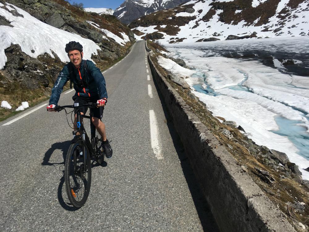 Cyclist passing a glacier in Norway