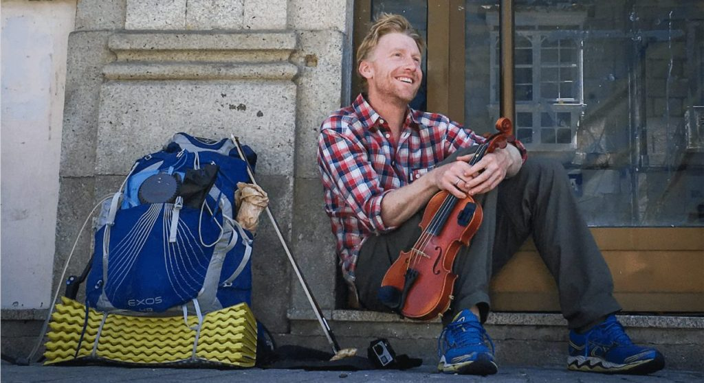 Alastair Humphreys in doorway with rucksack and violin