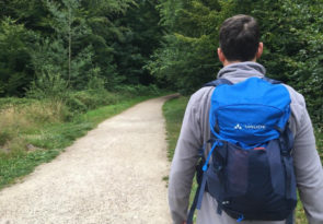 Man walking with small blue rucksack