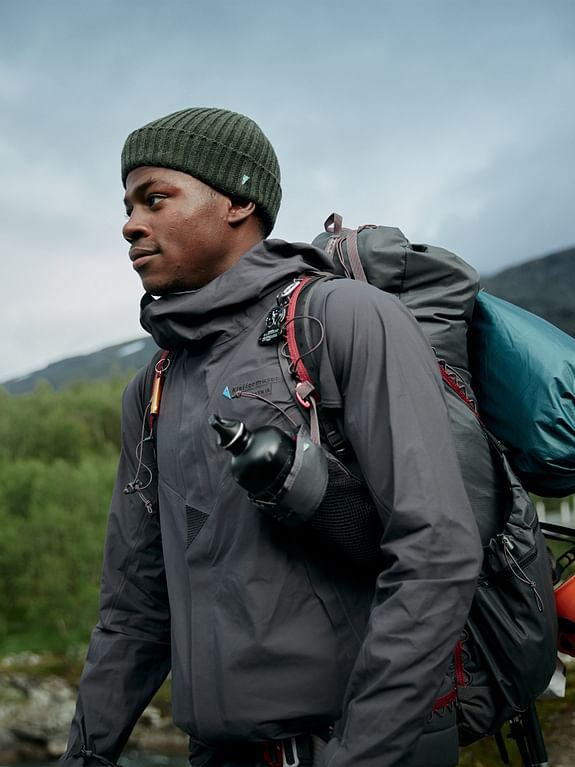 Man walking in mountains wearing black waterproof