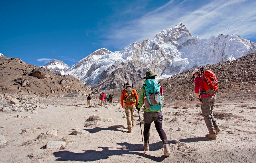 Group of walkers in mountains wearing essential summer outdoor gear and windproof clothing