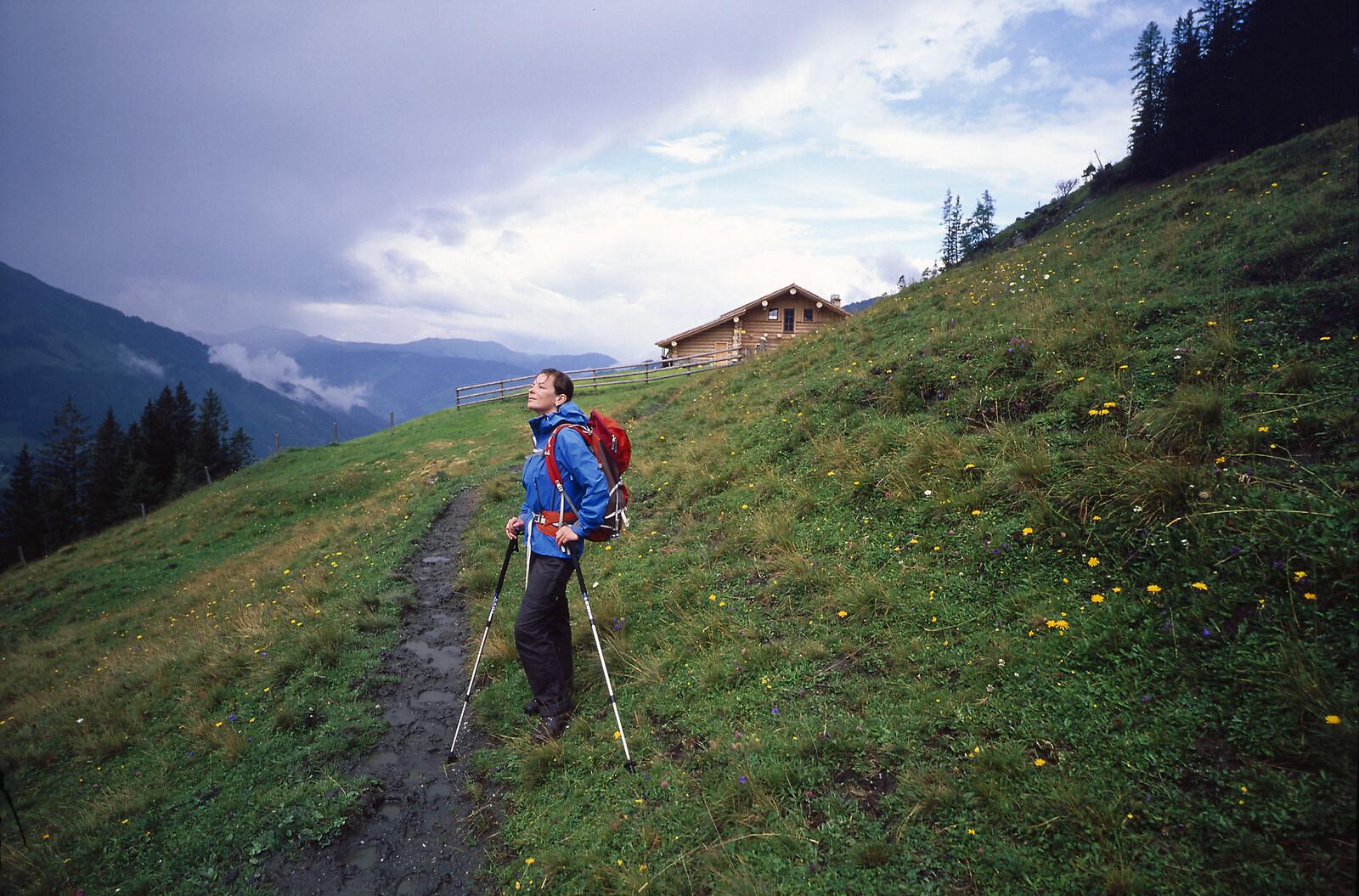 Woman walking up mountain track towards alpine hut in outdoor gear
