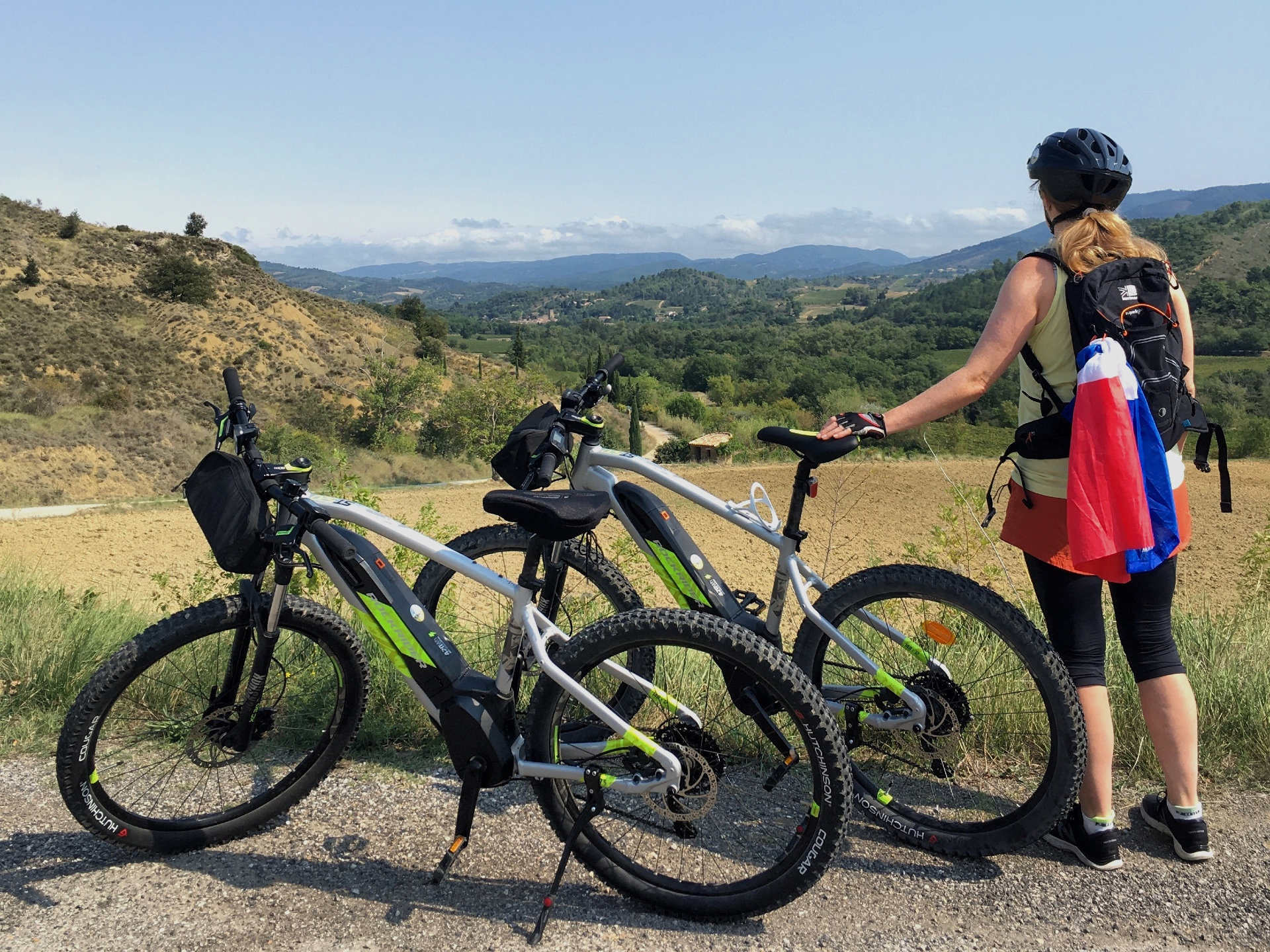 Cyclist with two ebikes looking at mountain views over Limoux